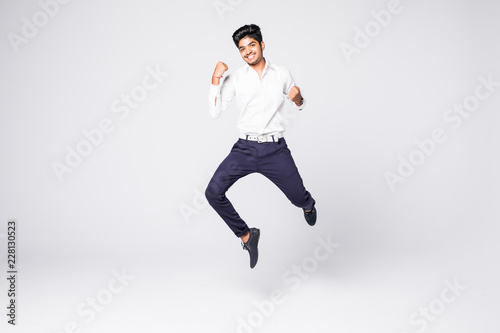 freedom, motion and people concept - indian young man jumping in air isolated on white