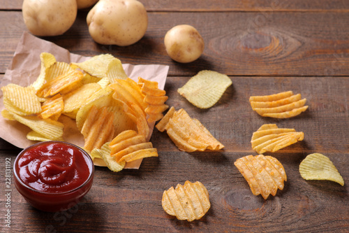 Valokuva  Chips with red sauce and fresh potatoes on a brown wooden table