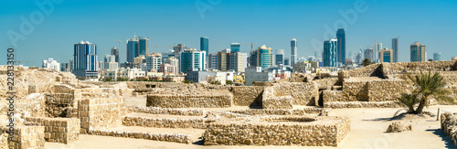 Poster Asia land Ruins of Bahrain Fort with skyline of Manama. A UNESCO World Heritage Site