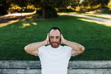 Man Covering Ears In Park