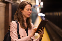 Business Woman In City Using Tablet Computer On Subway Platform