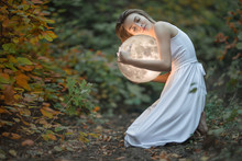 Beautiful Attractive Girl In A White Dress In The Autumn Forest, Hugs The Moon, A Mystery, A Mysterious Forest, Artistic Photography, With Space