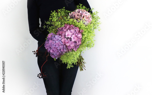 Women holding a colorful Autumn Bouquet with flowers like Hydrangea, Woodbine and Mantle.