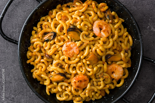 Traditional Spanish fideua. Noodle paella on black stone. Top view