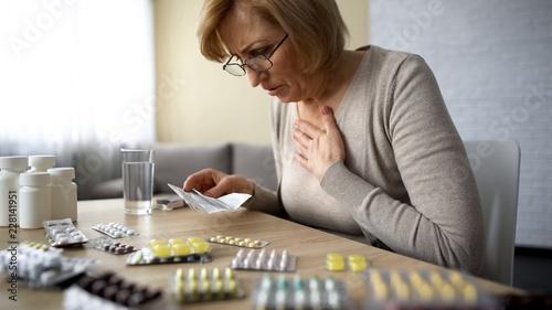Valokuva Senior lady feeling unwell, poor quality of medication dangerous self-medication