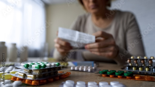 Medication lying on table, sick old woman reading prescription behind, closeup Canvas-taulu
