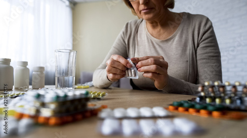 Valokuvatapetti Unhealthy elderly lady drinking pills, vitamins, illness symptoms, hypochondria