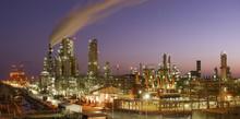 Illuminated Petrochemical Plant Against Sky During Sunset