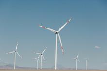 Windmills On Desert Against Bl...