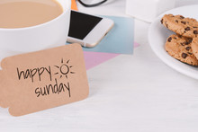 """Paper Card With """"happy Sunday"""" Text And Coffee With Phone, Cookies And Glasses"""