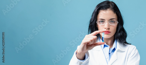 Fototapeta Laboratory scientist researcher with a test vial on a blue background