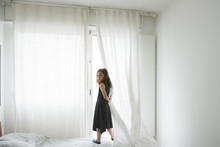 Portrait Of Girl Standing By Window On Bed At Home