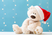 Teddy Bear Wearing A Santa Hat On A Shiny Light Blue Background
