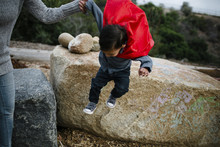 Midsection Of Mother Assisting Son In Jumping From Rock At Park