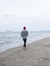 Rear View Of Man Jogging At Be...