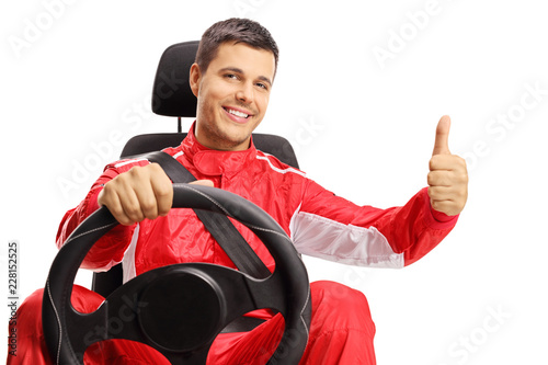 Race driver in a car seat making a thumb up sign