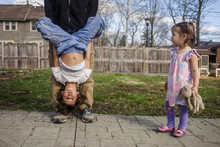 Cute Girl Looking At Father Carrying Brother Upside Down While Standing In Backyard