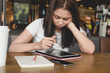 Young asian woman graphic designer using digital tablet, touch pen, smartphone on wooden table at cafe.