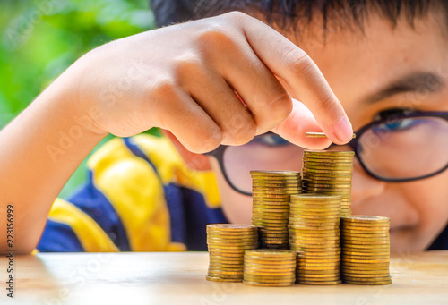 Photo The Asian boy stacking with coins to save the money for the future
