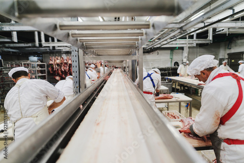 Fotografía Workers at meet industry handle meat organizing packing shipping loading at meat factory