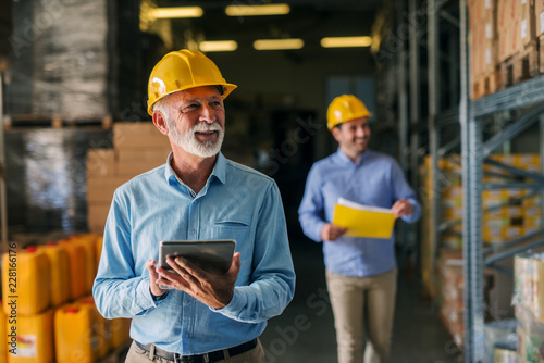 Photo  Picture of father and son walking through their warehouse with helmets on their heads