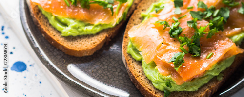Leinwand Poster Rye bread avocado toasts with smoked salmon on white wooden board