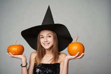 Closeup Of Playful Halloween Witch Holding Orange Pumpkins Looking Away At Copy Space, Isolated On Grey Background