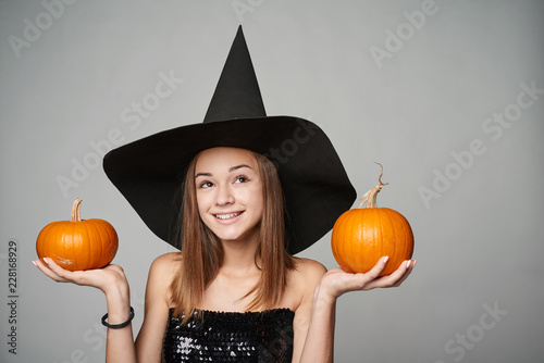 Photo Closeup of playful Halloween witch holding orange pumpkins looking away at copy