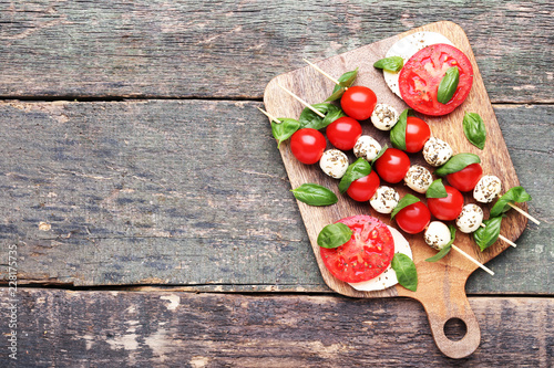Photo  Sticks with mozzarella, tomatoes and basil leafs on wooden cutting board