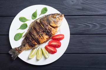 Fototapeta Fried fish dorado with lime , tomatoes and spinach