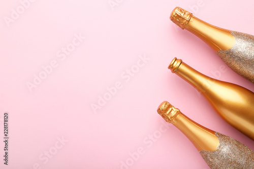 Decorated champagne bottles on pink background