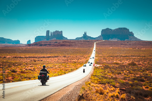 Foto op Plexiglas Verenigde Staten Biker on Monument Valley road at sunset, USA