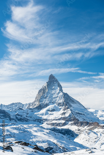 Scenic view on snowy Matterhorn peak in sunny day with blue sky and dramatic clo Wallpaper Mural