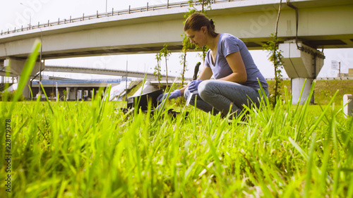 Valokuvatapetti Woman ecologist getting samples of plants near highway