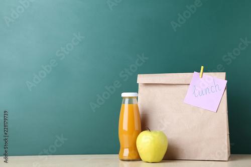 School lunch in paper bag on chalkboard background