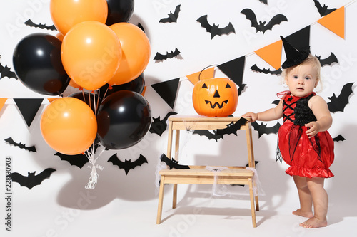 Photo  Baby girl in halloween costume with balloons and pumpkin bucket on white backgro