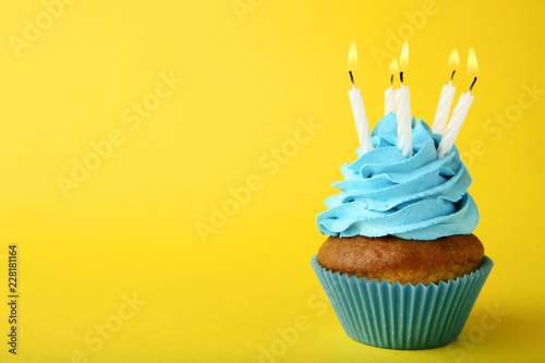 Tasty cupcake with candles on yellow background Wallpaper Mural