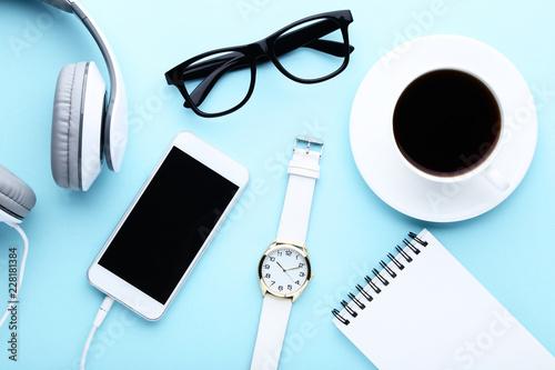 Fototapeta Smartphone with headphones, cup of coffee, notebook and glasses on blue background obraz na płótnie