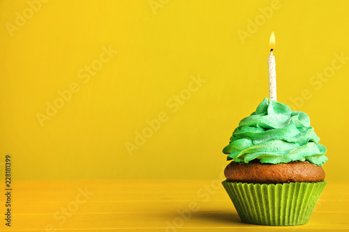 Tasty cupcake with candle on yellow background Canvas Print