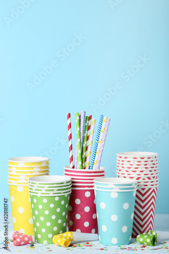 Colorful paper cups with straws and blowers on blue background