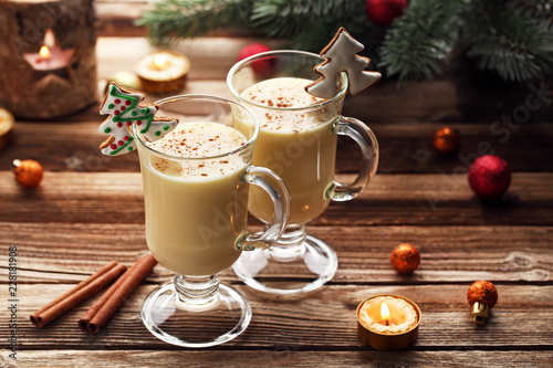 Eggnog in glasses with gingerbread cookies on wooden table