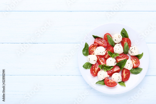 Photo  Mozzarella, tomatoes and basil leafs in plate on wooden table