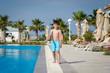 Smiling Caucasian boy having fun in swimming pool at resort. He is walking along pool edge.