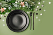 Christmas table setting. Black tableware and decoration with fir-tree branch. Flat lay, top view.