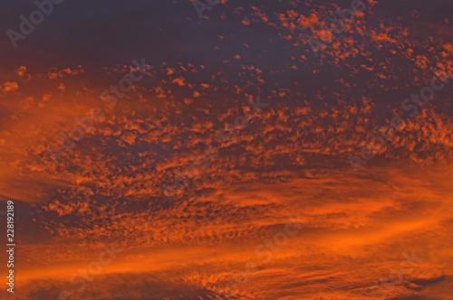 Fotografiet  Chmury zabarwione na czerwono światłem zachodzącego słońca.