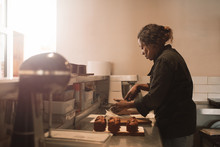 Baker Cutting Brownies At The Counter Of A Commercial Kitchen