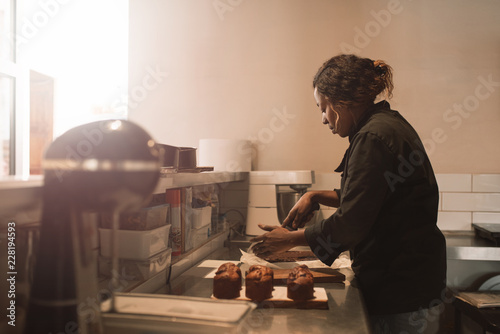 Baker cutting brownies at the counter of a commercial kitchen Poster Mural XXL