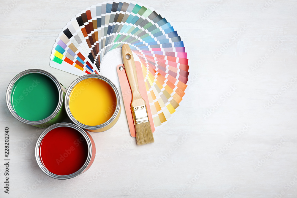 Fototapeta Cans with paint, brush and color palette on light background, top view. Space for text