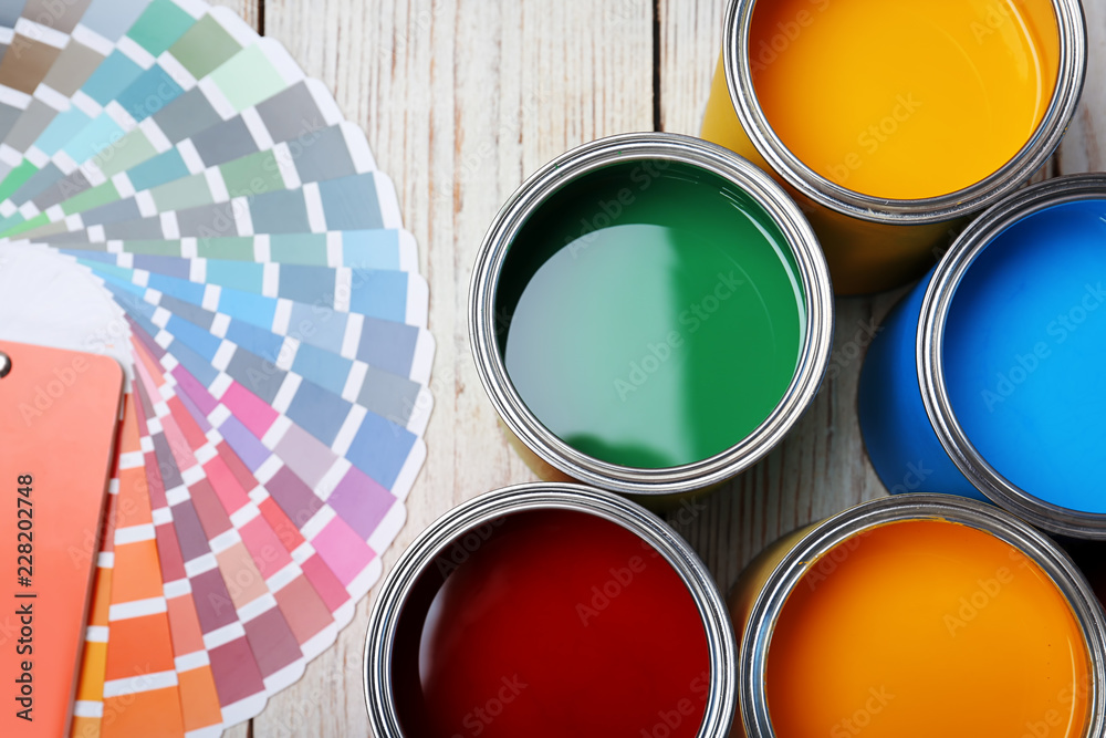 Fototapeta Cans with paint and color palette on wooden background, top view