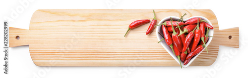 In de dag Aromatische Heart shaped bowl with red chili pepper on cutting board. Top view, space for text, white background